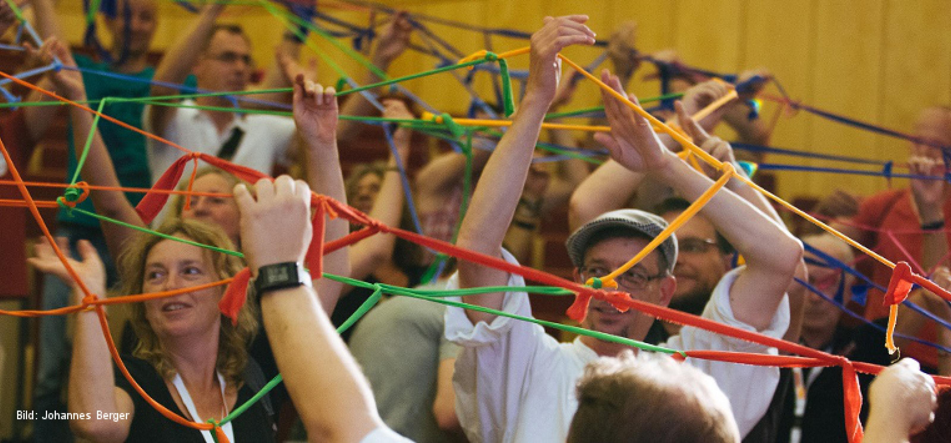 Viele Menschen in einem Konferenzsaal halten an ausgestreckten Armen ein Netz aus zusammengeknüpften bunten Bändern in die Luft