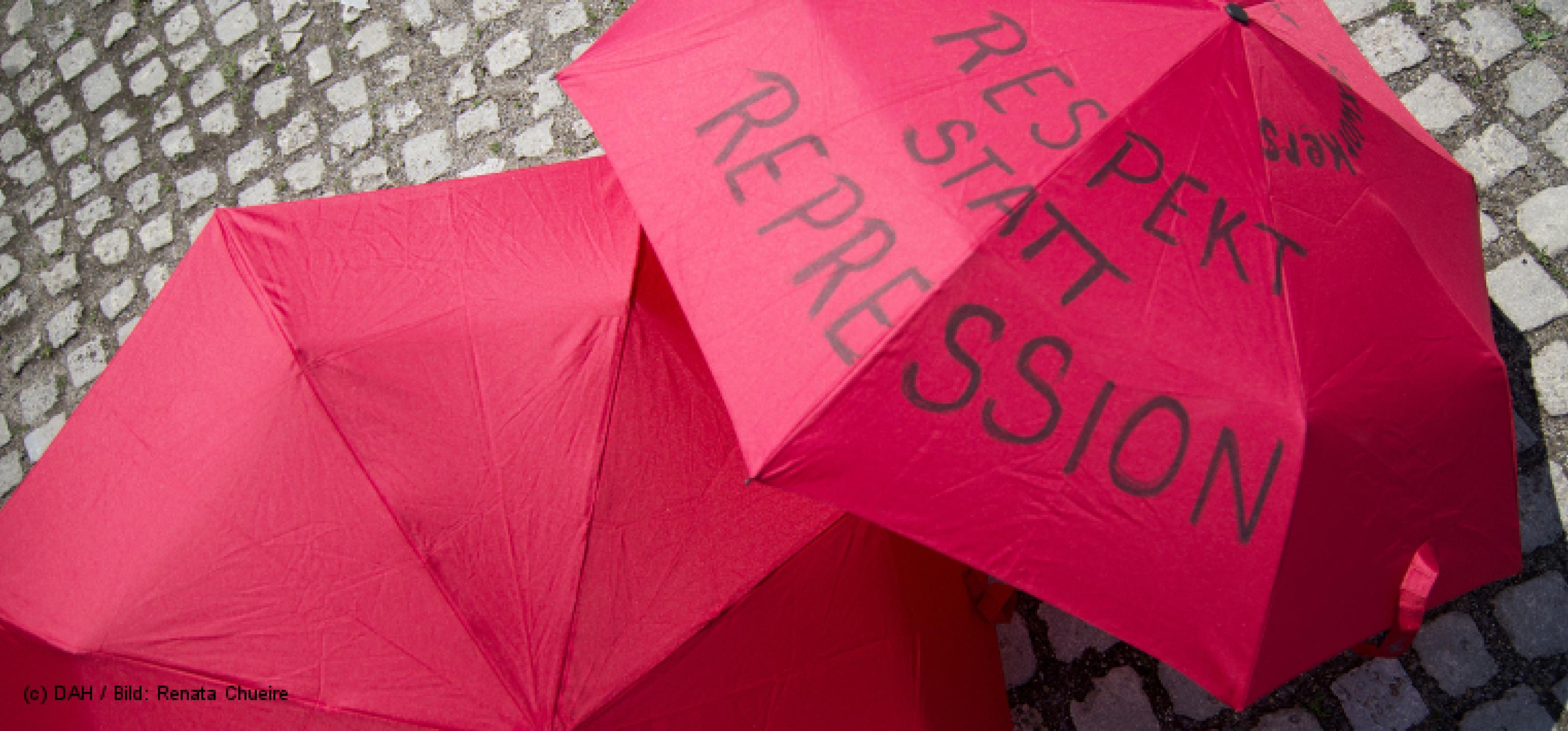 Zwei rote Regenschirme liegen aufgespannt auf Kopfsteinpflaster, auf dem rechten steht geschrieben: Respekt statt Repression
