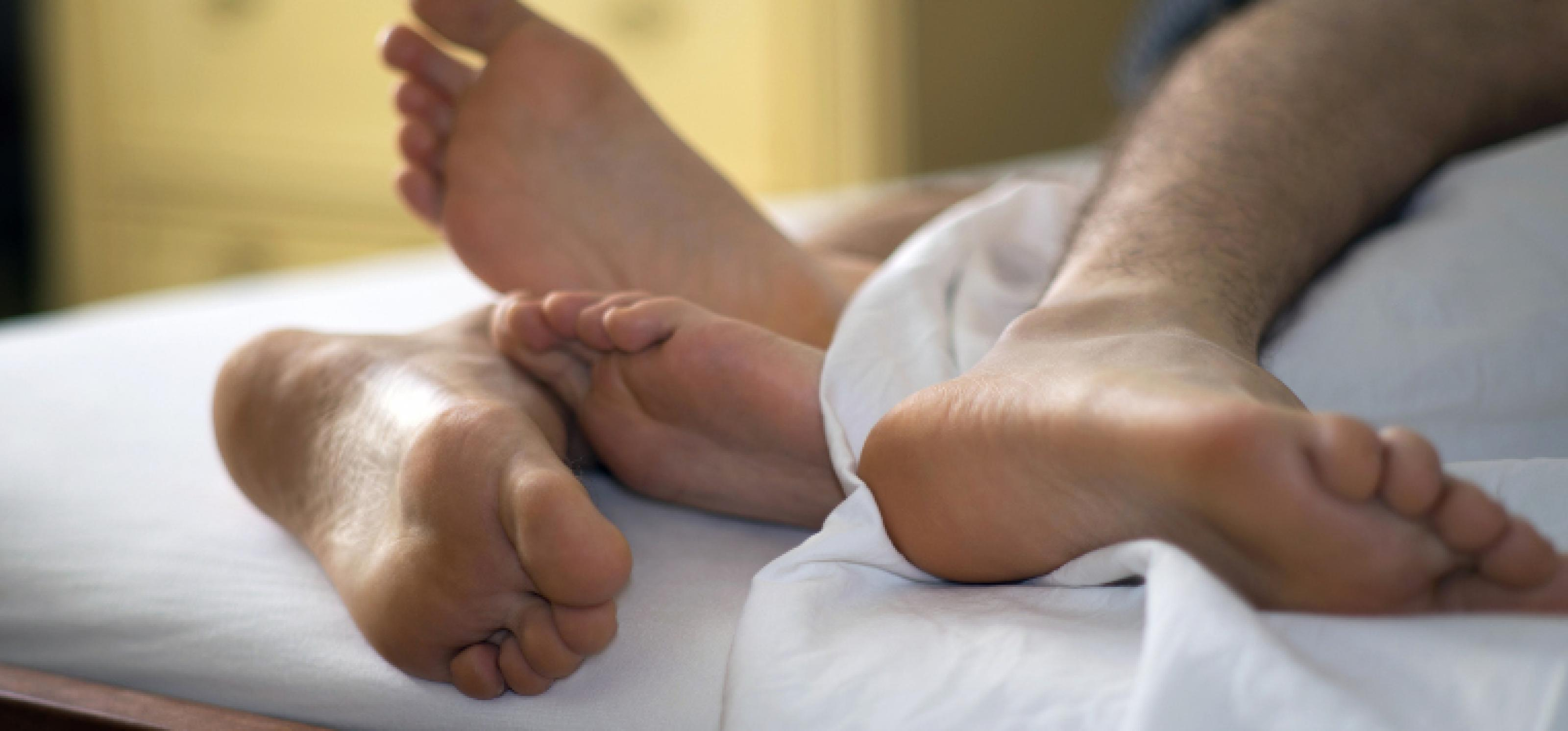 Zwei Paar Füße ragen unter einem Bettlaken hervor