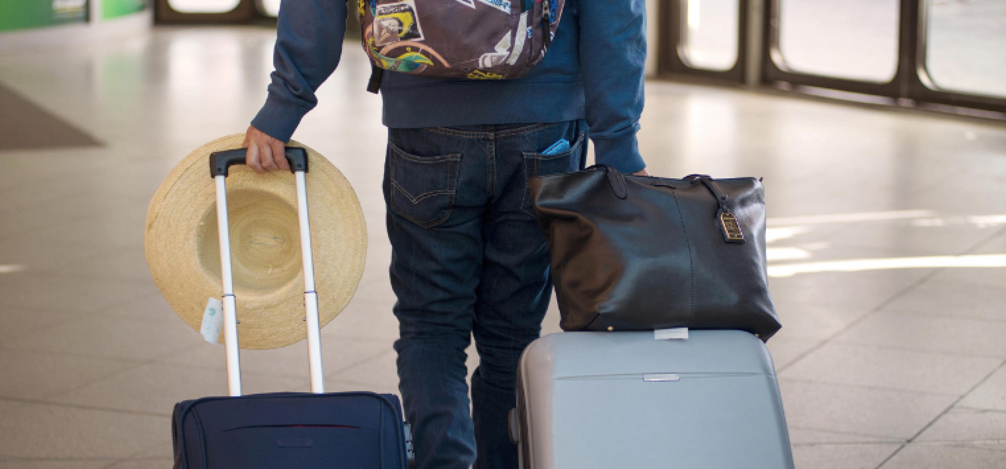 Ein Mann, von hinten fotografiert, zieht zwei Rollkoffer in einem Flughafengebäude hinter sich her
