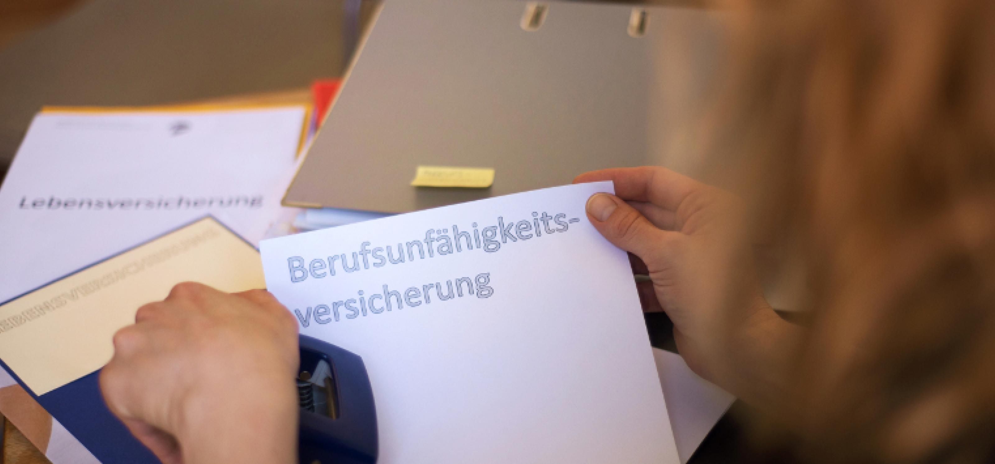 """Eine Frau sortiert Papiere mit der Aufschrift """"Berufsunfähigkeitsversicherung"""" in einen Ordner ein."""