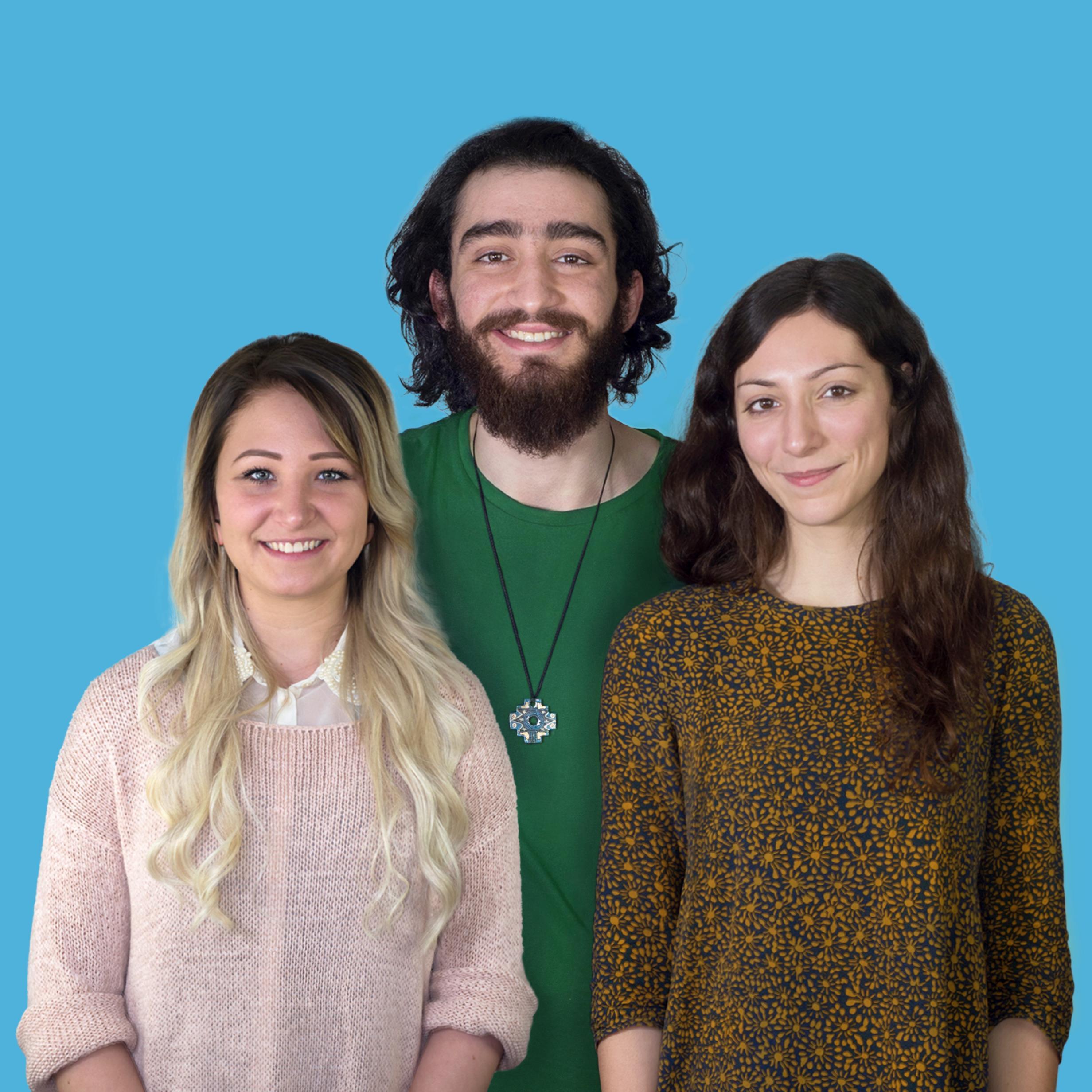 Eine Gruppe von drei Menschen: eine junge Frau mit langen blonden Haaren, ein Mann mit dunklen langen Haaren und Bart und eine Frau mit langen braunen Haare